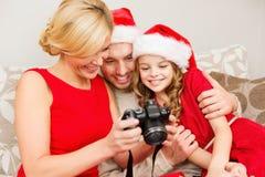 在圣诞老人看pictires的帮手帽子的家庭 免版税图库摄影
