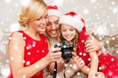 在圣诞老人看pictires的帮手帽子的家庭 免版税库存图片