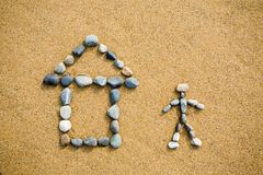 Pictogram. Of a house & person from a pebble on sand Stock Images