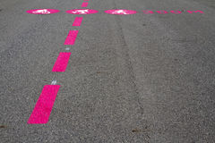 Pictogram lines. Pictograms and lines of biker, pedestrian and runner on a rough asphalt surface Stock Photo
