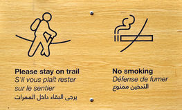 Pictograms for hikers. A signage carved on a wooden plate advising hikers to stay on the path and not to smoke, written below in English and Arabic Royalty Free Stock Image