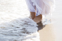 Pictore of feet on a beach and water. Stock Image