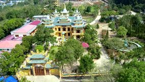 Aerial view yellow Buddhist gate and temple among garden. Pictorial aerial panorama yellow Buddhist complex with gate and right-angled temple under green roofs stock video footage