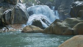 Small Foamy Waterfall Runs into Lake among Rocks. Pictorial close view small foamy waterfall runs into green river among stones and tropical plants stock video footage