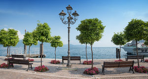 Pictorial lakeside promenade gargnano and garda lake, italy. Pictorial lakeside promenade gargnano, with orange trees and benches, garda lake, italy stock images