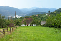 Pictorial landscape of mountain village with a palisade, Serbia. Pictorial landscape of mountain village with meadow, white house, palisade and Drina River in Stock Image