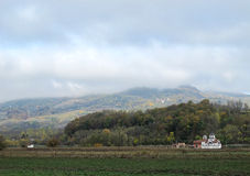 Pictorial landscape with a white church and foggy hills Stock Photography