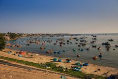 Pictorial Ocean with Fishing Boats near Sand Beach at Sunset. Pictorial azure ocean with traditional round Vietnamese fishing boats near sand beach at sunset Royalty Free Stock Photo