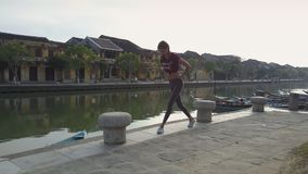 Beautiful girl trains doing squats near river in morning stock footage