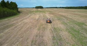 Fertilizer spreader moves to camera along harvested field. Pictorial picture fertilizer spreader moves to camera driving along vast striped harvested field stock video footage