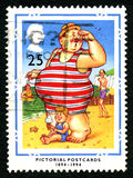 Pictorial Postcards UK Postage Stamp. GREAT BRITAIN - CIRCA 1994: A used postage stamp from the UK, celebrating traditional humorous seaside Pictorial Postcards Stock Photography