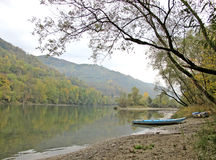 Pictorial river landscape with a blue boat. Pictorial autumn landscape of the river Drina in Serbia, with a blue boat at the riverside and colorful shadows in stock image