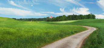 Pictorial rural landscape with winding country lane and little c Royalty Free Stock Photos