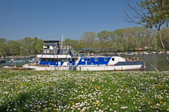 Pictorial spring landscape of ship, meadow and lake. Pictorial, beautiful spring landscape of colorful blue and white boat and flowers on the riverside of the Stock Photo