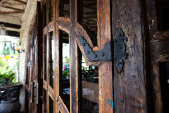 Pictorial style, wooden door with wrought-iron hinges and hook in famous restaurant Bali. Pictorial style, wooden door with wrought-iron hinges and hook in Royalty Free Stock Photos
