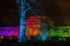 Pictorial view with lights projections at Kew Gardens, London. Pictorial view with lights projections at Kew Gardens, during Christmas time. Glass filter applied Stock Photos