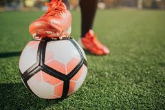 Pictre of man`s leg on football ball. Another one stand on green lawn. It is sunny outside. Pictre of man`s leg on football ball. Another one stand on green stock photo
