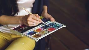 Pictrure d'aspiration d'artiste de jeune femme avec les peintures d'aquarelle et le plan rapproché de mélange de couleurs de bros Photos stock