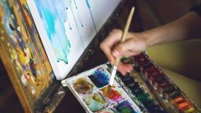 Pictrure di tiraggio dell'artista della giovane donna con le pitture dell'acquerello e spazzola sulla mano del primo piano della  fotografia stock libera da diritti