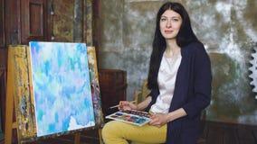 Pictrure di tiraggio dell'artista della giovane donna con le pitture ed il sorriso dell'acquerello che esaminano macchina fotogra immagini stock libere da diritti