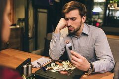 Pictue of guy sitting together with his girlfriend and eating some food they have ordered. Man has found some meat on. The plate. He is looking to the piece of stock image