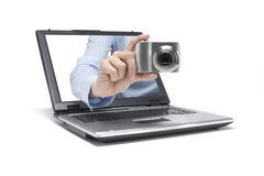 Picture. One hand reaches out of a laptop and takes a picture Stock Image