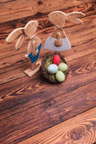 Picture from above of wooden easter bunnies near egg basket Royalty Free Stock Images