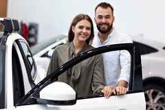 Adult couple choosing new car in showroom. Picture of adult couple choosing new car in showroom royalty free stock photos