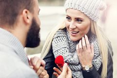 Adult man giving engagement ring to beautiful woman royalty free stock photo