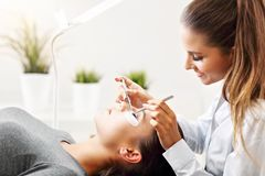 Adult woman having eyelash extension in professional beauty salon. Picture of adult women having eyelash extension in professional beauty salon stock photo