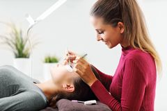 Adult woman having eyelash extension in professional beauty salon. Picture of adult women having eyelash extension in professional beauty salon stock photography