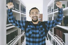 African student celebrating success in the library. Picture of African male college student celebrating his success by lifting hands in the library Stock Images