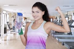 African woman holding a bottle. Picture of African woman holding a bottle while showing her bicep in the gym center Royalty Free Stock Image