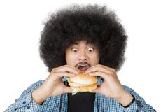 Afro man looks surprised with cheeseburger on studio. Picture of Afro man looks surprised while holding a big cheeseburger, isolated on white background Stock Photography