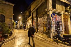 Building corner in Psyri district of Athens` city center, left to decay and ruin, with people walking in the dark. Picture of agion Anargion in the district of Royalty Free Stock Photos
