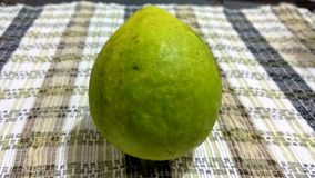 A guava on striped tablecloth. Picture of  alone  green guava, teardrop-shaped in the middle of creme color striped tablecloth Royalty Free Stock Images