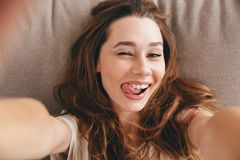 Picture Amazing happy emotional pretty lady make selfie. Picture of young amazing happy emotional pretty lady lies on sofa indoors. Looking camera make selfie Stock Photography