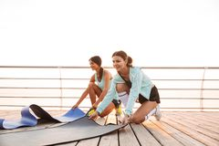 Two sports women friends outdoors on the beach with carpet. royalty free stock images