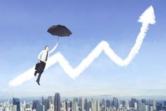 American businessman with umbrella and growth chart. Picture of American businessman using an umbrella to flying with clouds shaped a growth chart Royalty Free Stock Image