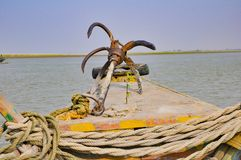Picture of an anchor in the front of a boat in a river..with ropes and a tire.. royalty free stock images