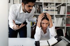 Picture of angry boss criticizing his worker. For doing bad work royalty free stock image