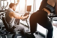 A picture from another angle where girl`s back is seen. Also there is her boyfriend working hard on the exercise bike as Royalty Free Stock Photos