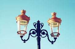 Picture of an antique street lamp against blue sky. vintage filtered image Stock Images