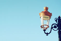 Picture of an antique street lamp against blue sky. vintage filtered image Royalty Free Stock Photo
