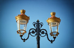Picture of an antique street lamp against blue sky. vintage filtered image Royalty Free Stock Photos