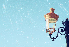 Picture of an antique street lamp against blue sky. vintage filtered image and bokeh lights Royalty Free Stock Photos