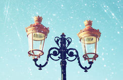 Picture of an antique street lamp against blue sky. vintage filtered image and bokeh lights Stock Photos