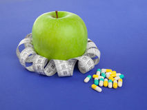 Picture of apple, pills and tape measure Royalty Free Stock Photos