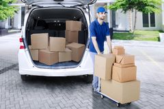 Arabian courier carrying packages with trolley Royalty Free Stock Images