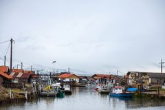 Oyster farmers huts in Gujan Mestras port on the Atlantic ocean during a cloudy rainy afternoon on Arcachon Bay, Bassin d`Arcachon. Picture of Arcachon Bay baie Stock Images